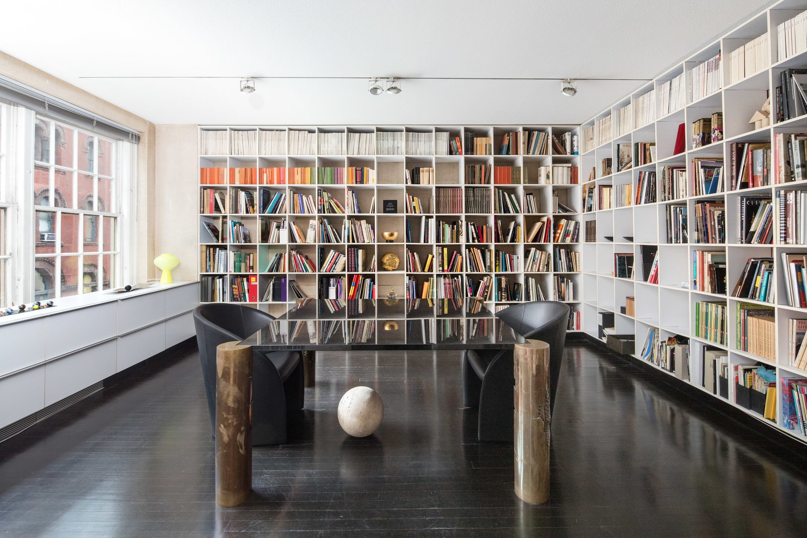 Office, Desk, Bookcase, Shelves, Study Room Type, Dark Hardwood Floor, Chair, Library Room Type, and Storage Lella Vignelli's office is lined with bookshelves. She designed the desk with legs fashioned by sculptor Arnaldo Pomodoro. The couple were known to host many cultural luminaries in the apartment, including Pomodoro and philosopher Umberto Eco.  Photo 4 of 9 in Legendary Designers Massimo and Lella Vignelli's New York Duplex Is Listed at $6.5M