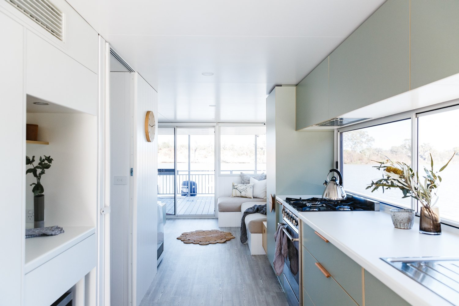 "Living Room, Vinyl Floor, Bench, Sectional, and Recessed Lighting ""Selection of materiality was critical in creating the illusion of more space than the actual footprint of the houseboat,"" Harry said.  Photo 3 of 14 in Life in This Renovated Houseboat Would Be But a Dream"