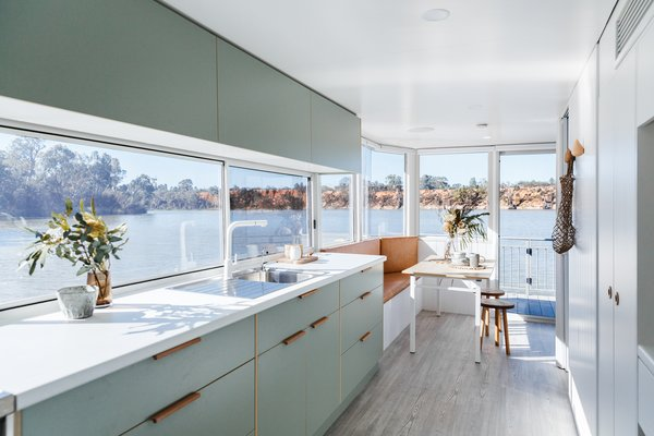 The design of this Australian houseboat features a soft, modern color palette. Here, light sage laminate kitchen cabinets are paired with leather recessed pulls.