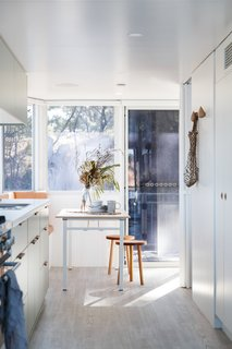 """Vinyl flooring in a soft driftwood color underscores a dining table that can seat up to eight. Harry selected warm leather for the banquette seating for its """"texture and timeless patina."""""""