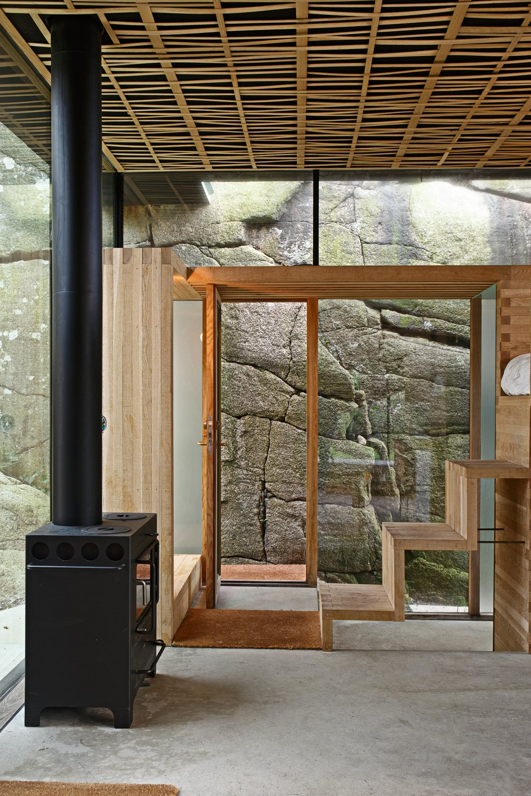 Living Room, Wood Burning Fireplace, and Concrete Floor Oak steps lead to the loft bed.  Photo 4 of 8 in This Norwegian Cabin's Roof Doubles as an Observation Deck