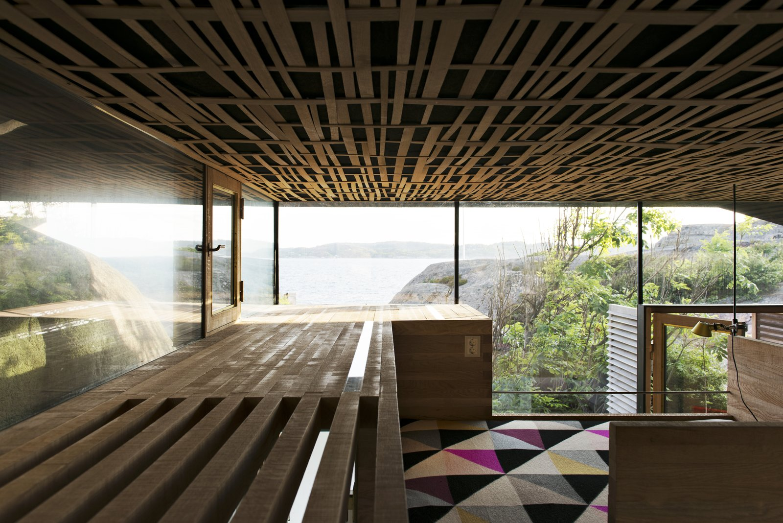 Bedroom, Bench, and Bed The interior walls are solid 50/50mm oak layered with a natural sawn texture, while the acoustic ceiling is covered with woven oak strips.   Photo 8 of 8 in This Norwegian Cabin's Roof Doubles as an Observation Deck