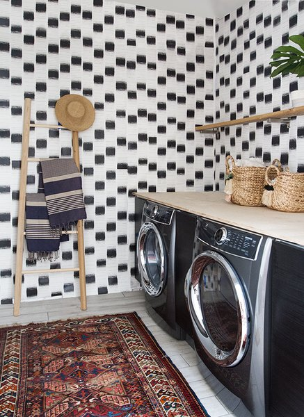 The laundry room features custom wallpaper designed by Samuel.