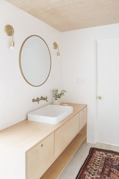 Samuel designed the custom vanity simply adorned with a Kohler Vox sink. The wall-mounted faucet is the Kohler Purist line and sconces are Cedar & Moss.