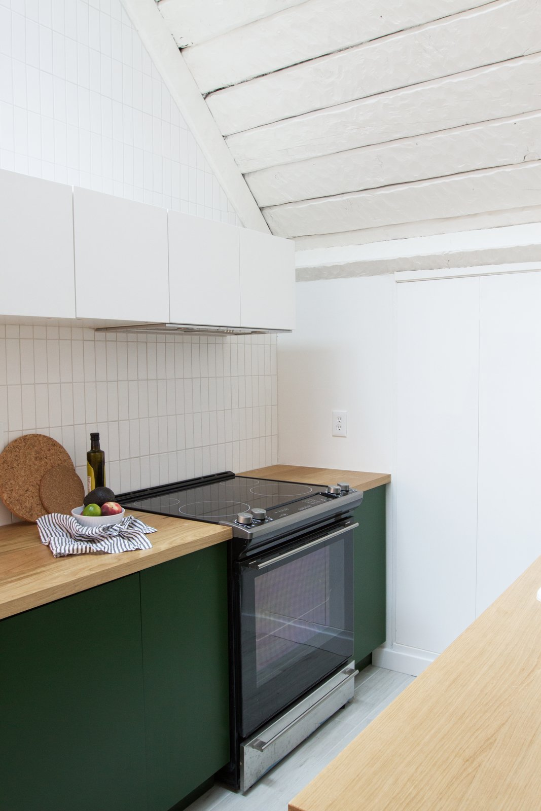 Kitchen, Range Hood, Wood, Ceramic Tile, Colorful, Porcelain Tile, Wall Oven, and Cooktops Samuel carried the handmade Fireclay tile up to the ceiling and painted the walls Polar Bear by Behr.  Best Kitchen Range Hood Colorful Photos