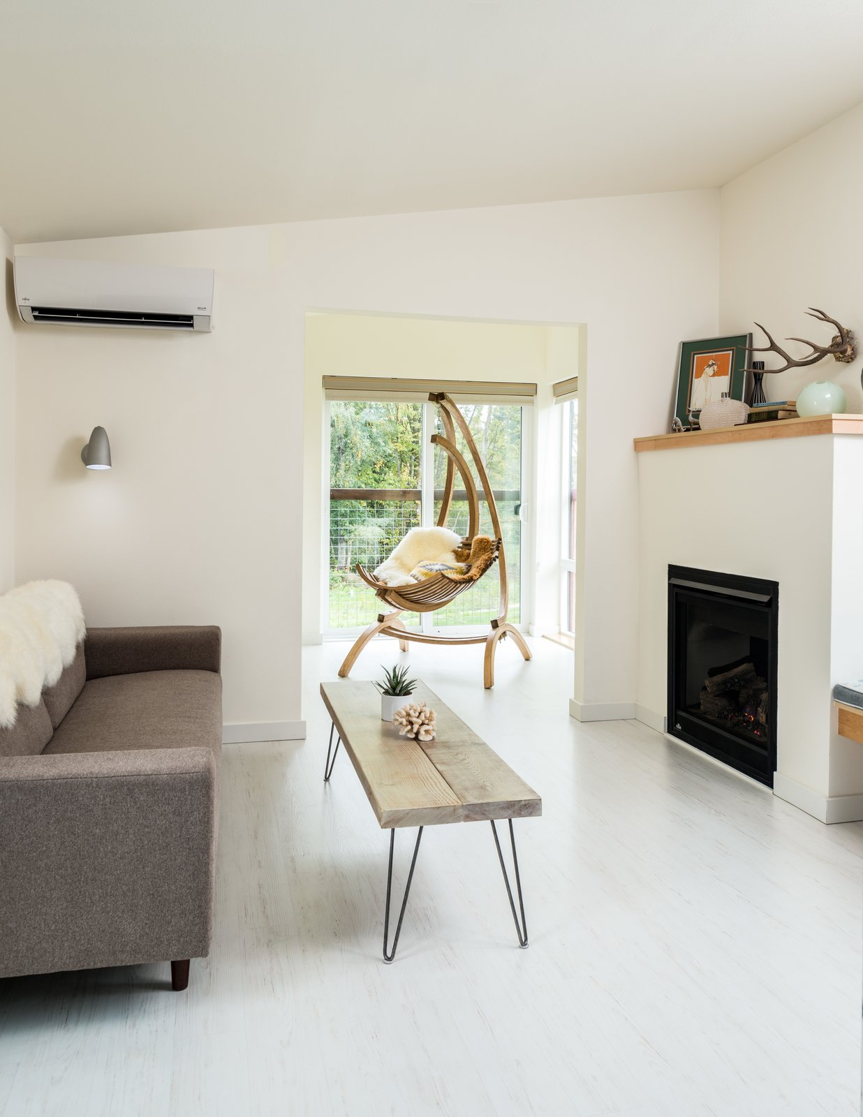 Living Room, Sofa, Coffee Tables, Light Hardwood Floor, Chair, Gas Burning Fireplace, and Wall Lighting A lodge with two seating areas.  Photo 3 of 7 in Serenity Awaits at These Prefab Cabin Rentals on Vashon Island