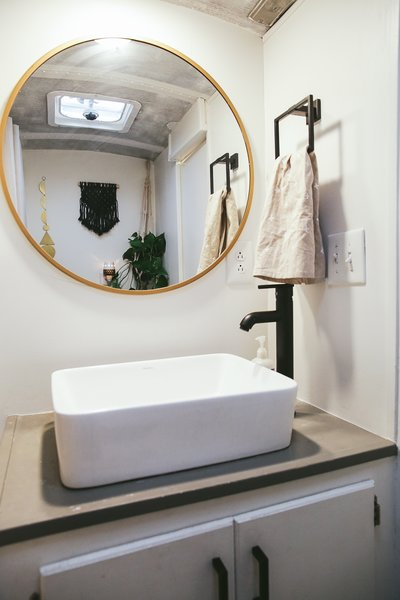 The Mayes did not want to separate the fixtures in the bathroom, so this one hosts the sink, toilet, and a shower. The brass mirror bounces light in the small space.