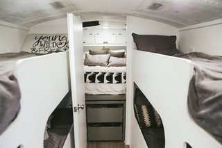 "There are four bunks for the kids' sleeping area, fitted over the wheel wells, and a door separates the parents' bedroom at the back of the bus. The mattress is positioned over the engine, so it is high, and there is clothing storage below it, on either side of the bed, and in wall cabinets above. The couple writes on their blog: ""Our bedroom has so much storage we haven't even used all of it!"""