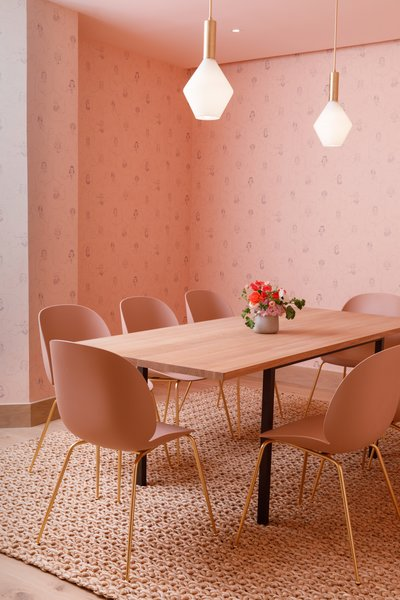 At the Brooklyn outpost of The Wing, the all-women co-working space, a meeting room is swathed in a mature color palette of monochromatic pinks with matching un-upholstered Beetle chairs. The walls are covered with wallpaper depicting the the face of women.