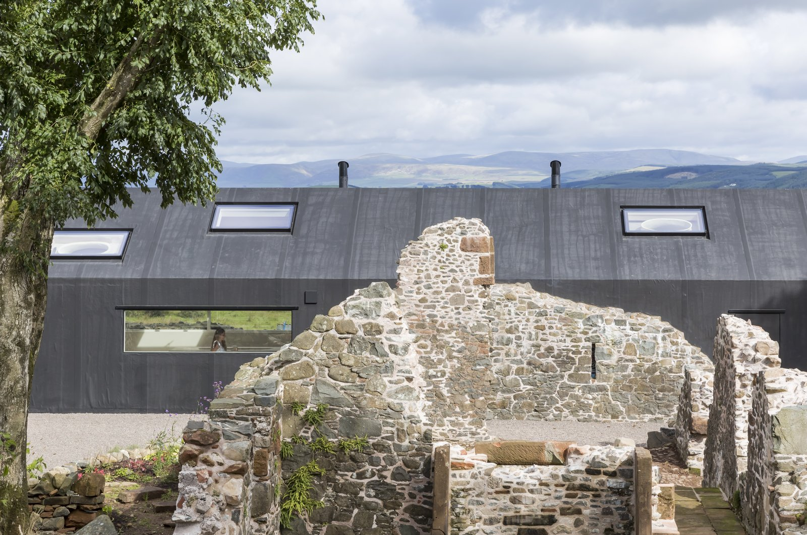 Exterior, House, Green, Farmhouse, Vinyl, Gable, and Stone The building's modern exterior cladding contrasts dramatically with the existing ruins.   Best Exterior Green Vinyl Photos from This Renovated Scottish Farmhouse With Sinuous Interior Walls Is a Jaw-Dropper