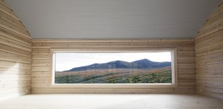 """The panorama window in the barrel-vaulted living room. """"The low position of the window emphasizes that this is a room to sit and relax,"""" says the architects. This room was built with 19th-Century notched logs."""