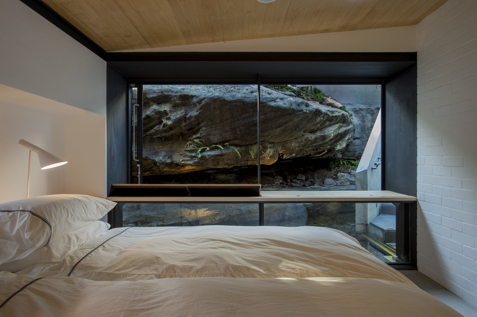 Bedroom, Lamps, Bed, Concrete Floor, Shelves, and Table Lighting The rock ledge provides natural privacy from the street and ensconces occupants in the site's beauty.  Photo 7 of 8 in An Arresting Australian Abode by Glenn Murcutt Needs a Buyer