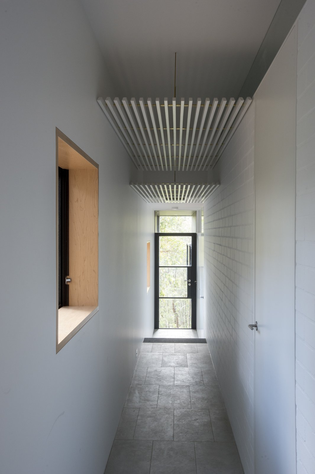 Hallway and Concrete Floor Passageways take advantage of the Southside of the house, so that living areas and bedrooms receive Northern sunlight. White walls are satin-finished or bagged brickwork.  Photo 4 of 8 in An Arresting Australian Abode by Glenn Murcutt Needs a Buyer
