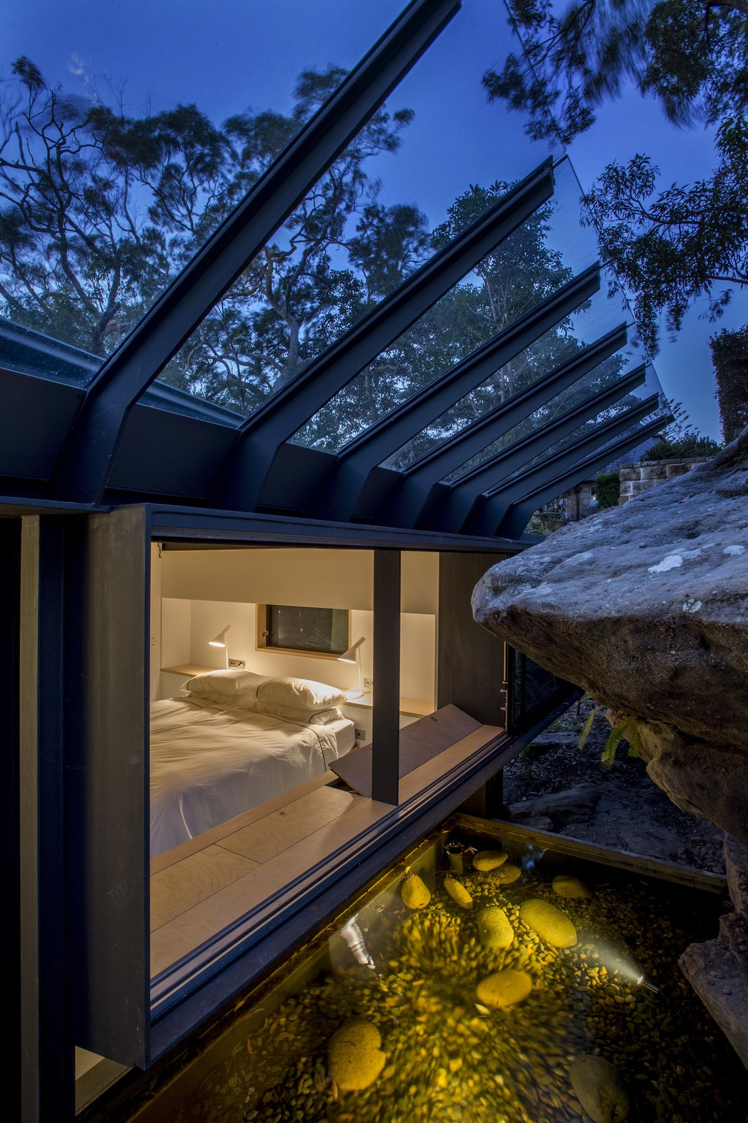 Bedroom, Bed, Table Lighting, Shelves, Concrete Floor, and Night Stands The principle bedroom windows embrace the sandstone rock face. A sloped glass roof shields rain.  Photo 6 of 8 in An Arresting Australian Abode by Glenn Murcutt Needs a Buyer