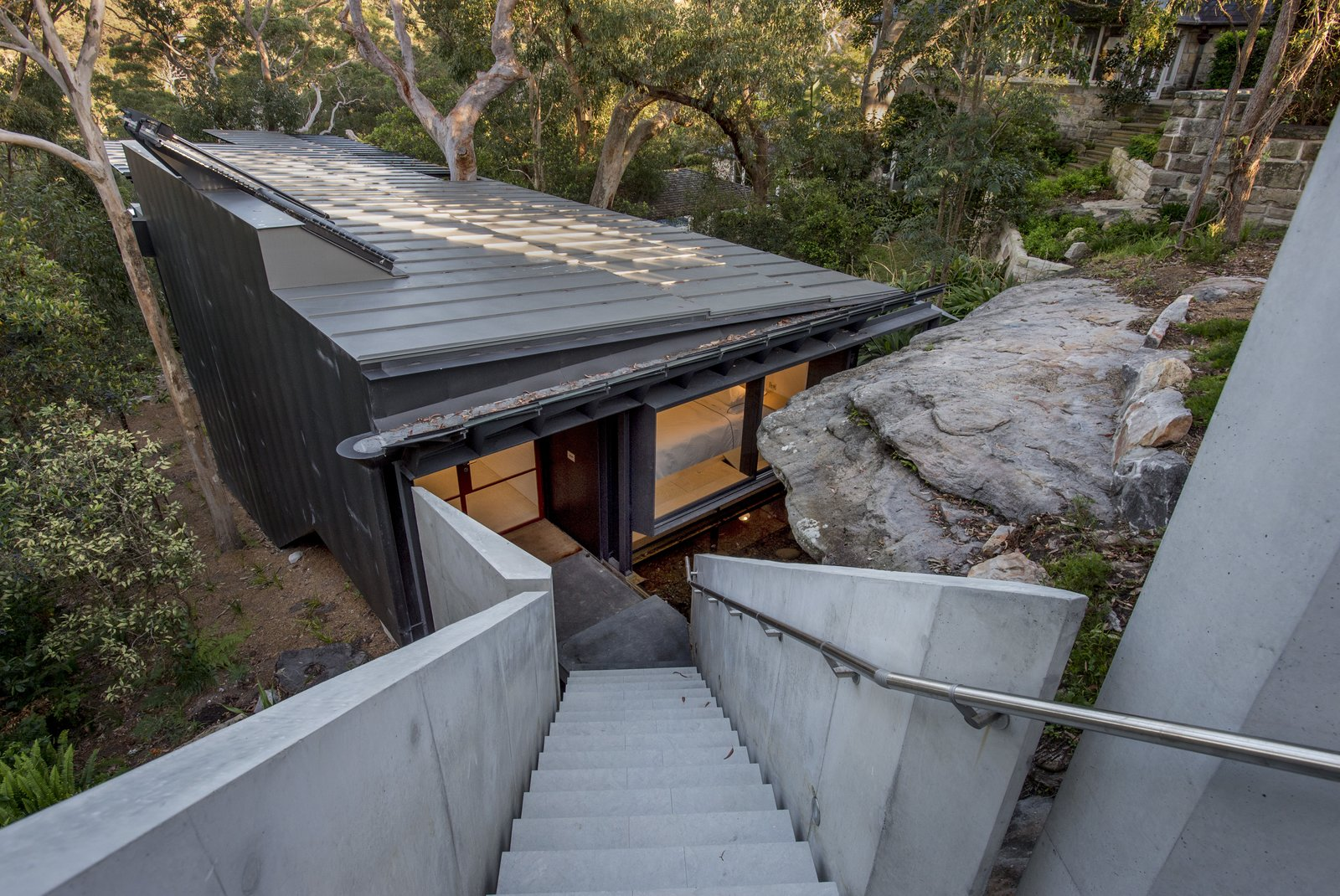 Outdoor, Front Yard, Trees, Walkways, Concrete Fences, Wall, and Boulders The house sits on a steep site and was positioned below a sandstone crop so as to be concealed from the street. The approach to the house is via a suspended concrete staircase.  Photo 1 of 8 in An Arresting Australian Abode by Glenn Murcutt Needs a Buyer
