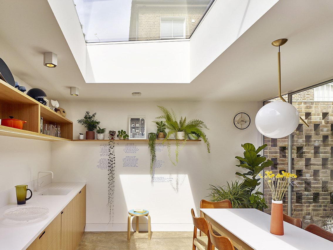 Kitchen, Wood Cabinet, Undermount Sink, Pendant Lighting, Ceiling Lighting, and Concrete Floor In the combined kitchen and dining room, a skylight lets in lots of sunlight, and the table overlooks the courtyard.  Best Photos from A Perforated Brick Facade Shields a Glowing London Infill Home