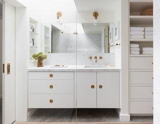 A Carrara marble counter and backsplash, concrete floors, a frameless mirror, and white cabinets keep the look seamless and consistent in the bathroom.