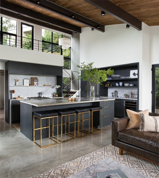 The entry segues into the open kitchen and living space. The second-floor mezzanine was once enclosed. By removing its walls, the architects brought in more light and a better connection to the outdoors.