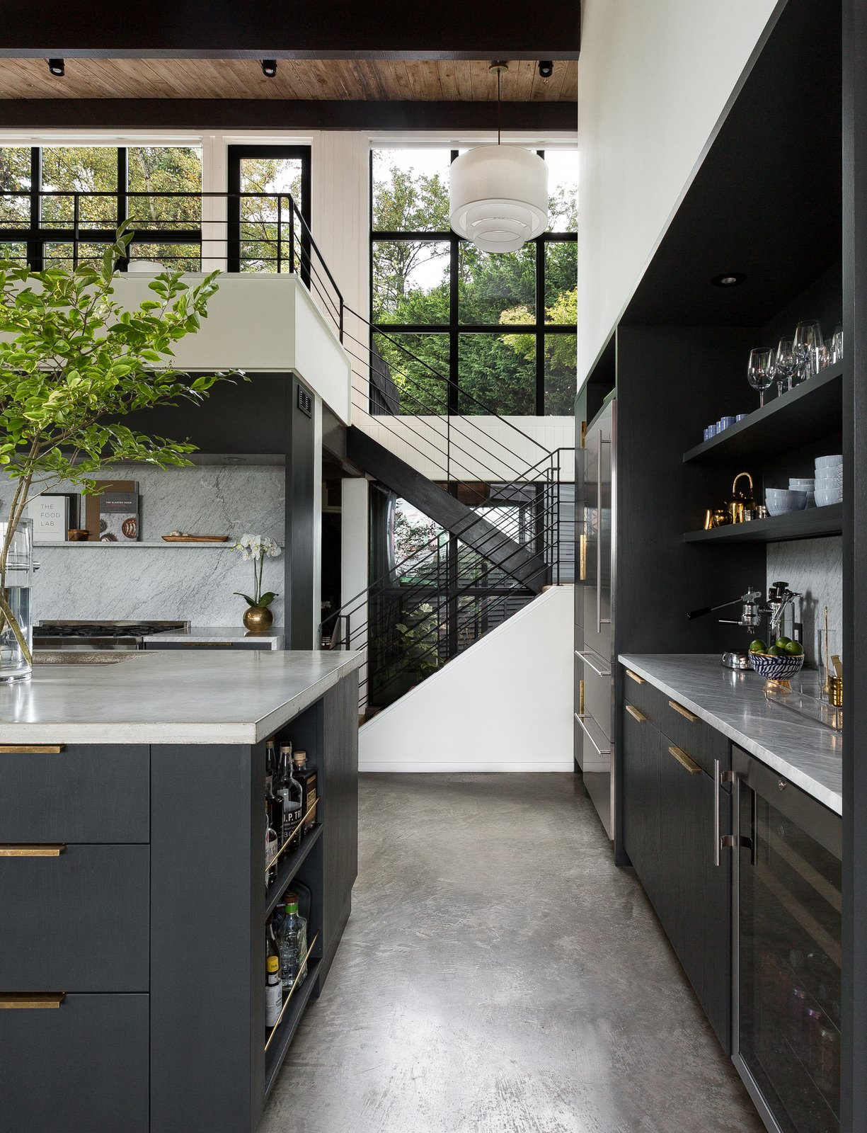 Montlake House kitchen hallway with concrete floors and brass pulls on cabinets