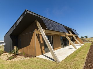 """A """"raked roof"""" promotes daylighting, while a 6Kw photovoltaic solar array with 4.8Kw battery storage generates clean energy. The front porch encourages socializing with the neighbors."""