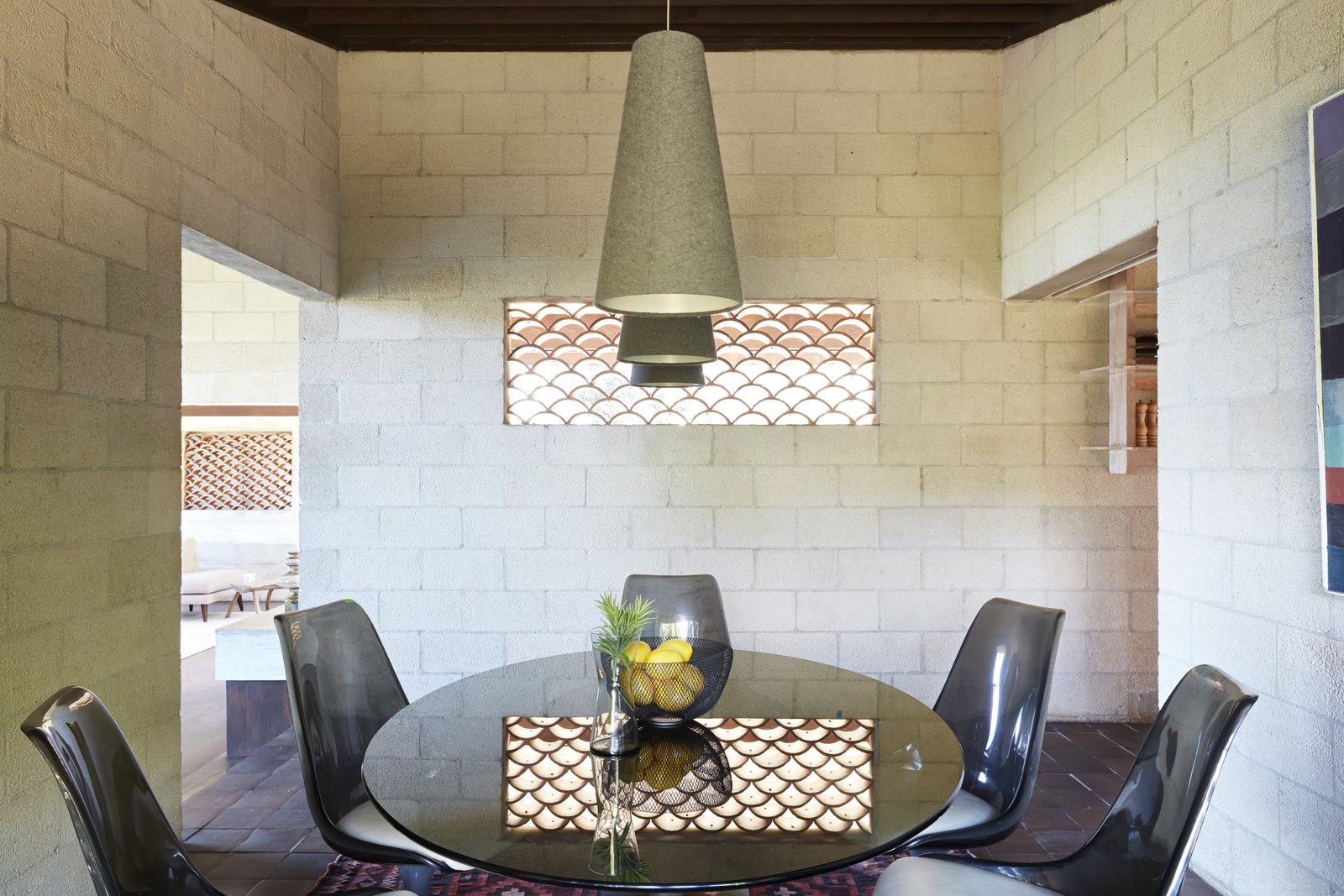 Dining Room, Chair, Table, Ceramic Tile Floor, and Pendant Lighting Light and air transmits through the wall cut-out in the dining room.  Photo 11 of 19 in A Famed Japanese Composer's Effortless Honolulu Hideout Asks $2.95M