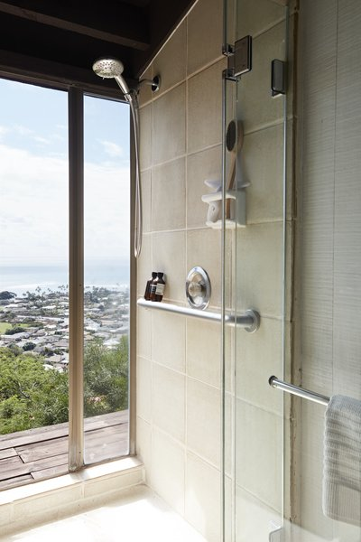 A shower with floor-to-ceiling glazing fosters indoor/outdoor flow.