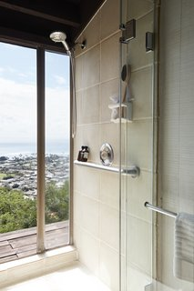 A shower with floor-to-ceiling glazing fosters indoor/outdoor flow.