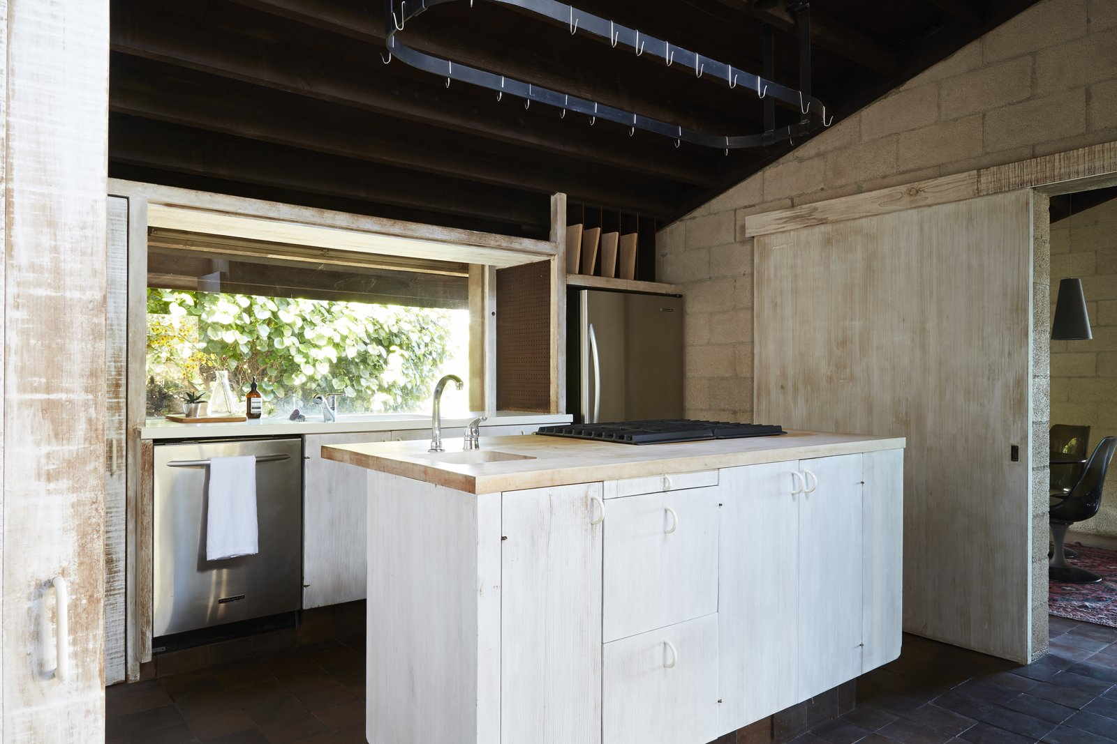 Kitchen, Dishwasher, White Cabinet, Ceramic Tile Floor, Wood Cabinet, Wood Counter, Range, Refrigerator, and Drop In Sink In the kitchen, rough-cut wood was treated to give it a bleached look that contrasts with the dark ceiling.  Photo 9 of 19 in A Famed Japanese Composer's Effortless Honolulu Hideout Asks $2.95M