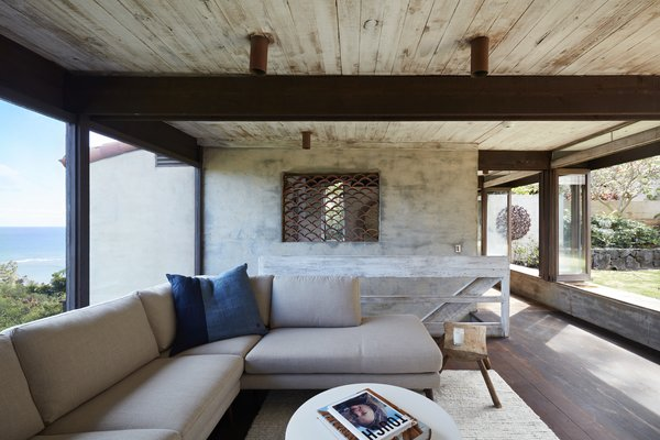 The living room is a cozy spot nestled between the expansive picture window and open doors that lead to the courtyard.