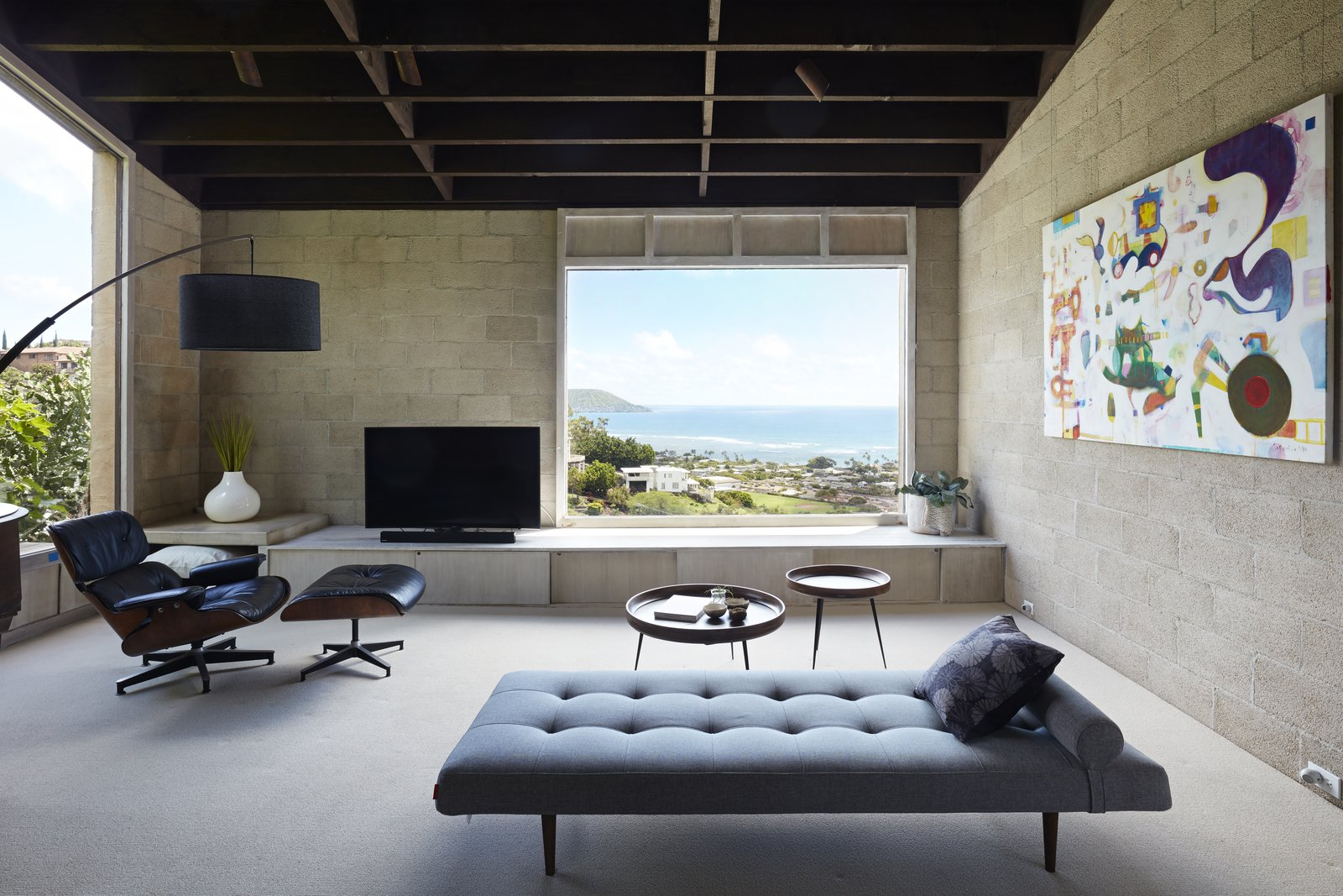 Living, Recliner, Coffee Tables, Ceiling, Carpet, Bench, Chair, Floor, and Ottomans Large picture windows in every room connect occupants to Pacific Ocean vistas.   Best Living Carpet Ottomans Photos from A Famed Japanese Composer's Effortless Honolulu Hideout Asks $2.95M