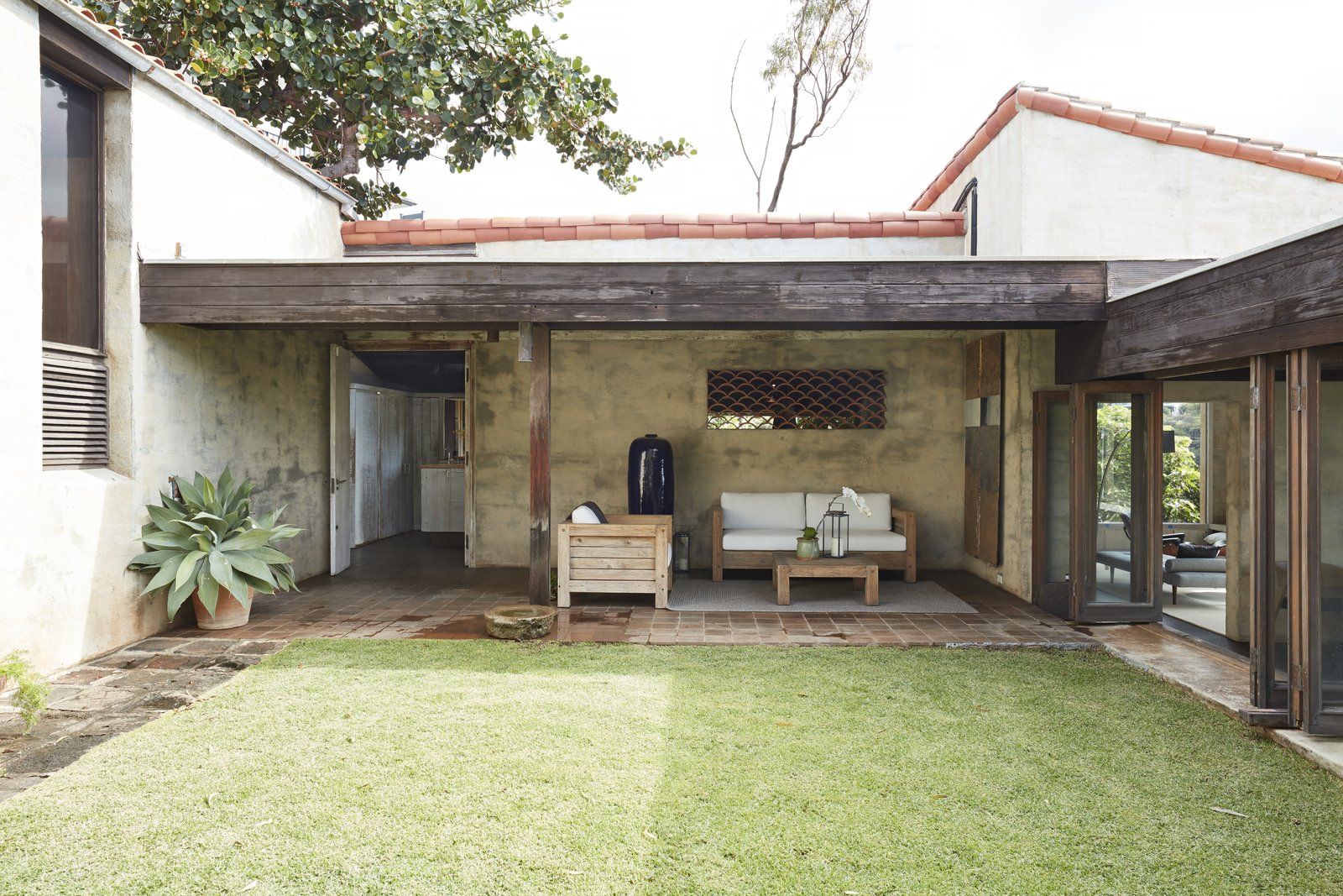 Outdoor, Planters Patio, Porch, Deck, Grass, Back Yard, and Tile Patio, Porch, Deck A view of the lanai with the kitchen behind it.  Photo 8 of 19 in A Famed Japanese Composer's Effortless Honolulu Hideout Asks $2.95M