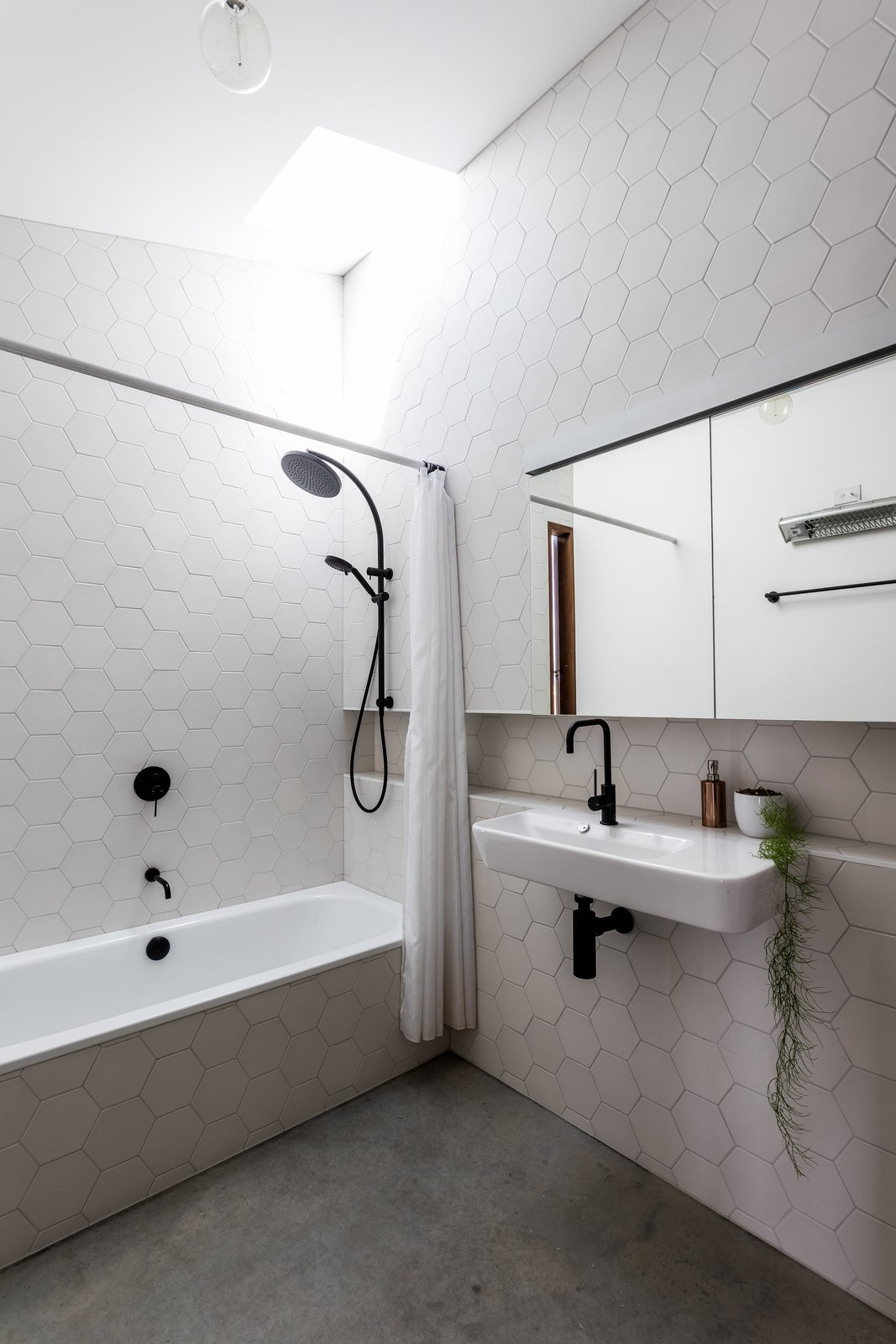 Bath, Concrete, Wall Mount, Alcove, Ceramic Tile, Pendant, and Full The finish palette in the bathroom relates to the kitchen for consistency.  Best Bath Alcove Ceramic Tile Concrete Photos from An Architect's 1958 Midcentury in Tasmania Gets a Graceful Renovation