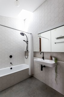 The finish palette in the bathroom relates to the kitchen for consistency.