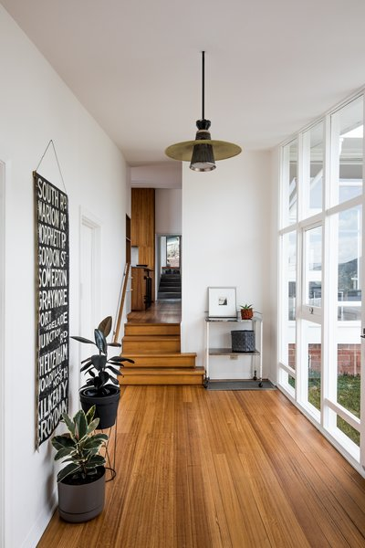 Inside the entry, looking through the house towards the extension, Emery's original palette combined white walls with wood floors.