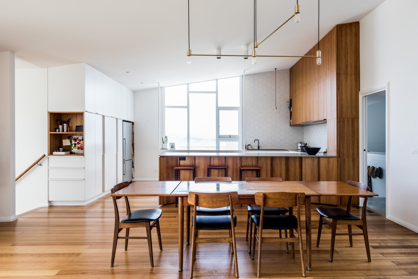 """Kitchen, Concrete, White, Wood, Refrigerator, Medium Hardwood, Ceiling, Pendant, and Ceramic Tile In this Tasmanian midcentury, the architects gently reworked the interior layout, replacing a small sitting room and bath/laundry with a new kitchen. The kitchen's wood cabinetry """"references the original timber joinery elsewhere,"""" write the architects.  Best Kitchen Wood Refrigerator Concrete Photos from An Architect's 1958 Midcentury in Tasmania Gets a Graceful Renovation"""