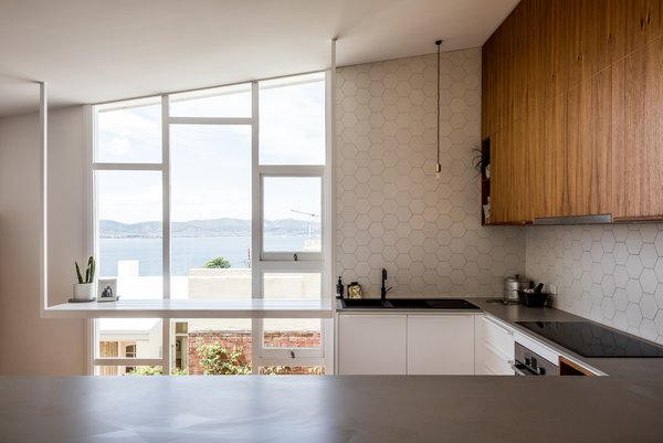 The kitchen's new position takes advantage of morning light. Note how the white countertop doesn't disturb the original windows.