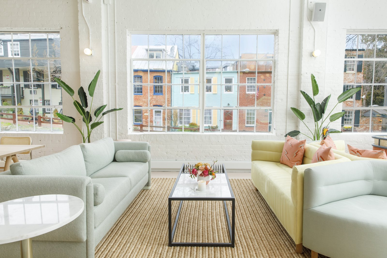 Living Room, Wall Lighting, Rug Floor, End Tables, Light Hardwood Floor, Sofa, Coffee Tables, and Chair The pastel-colored couches echo the facades on the row houses lining the C&O Canal outside.    Photo 11 of 13 in Feast Your Eyes on Washington D.C.'s Newest Co-Working Space For Women