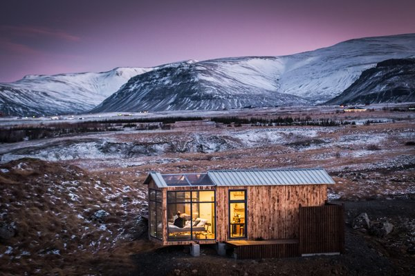 """The motto for the Panorama Glass Lodge states """"Where the sky is,"""" which works as a fitting descriptor for the design of this cozy 248-square-foot vacation cabin. Thanks to the glass panels that wrap around a strategically placed bed, the bright dancing lights of the aurora can be viewed from the most comfortable spot."""