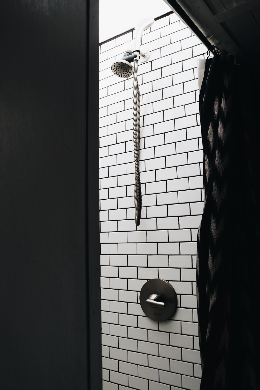 """Bath Room, Subway Tile Wall, and Corner Shower The couple improved the shower before moving back on the bus full-time by enlarging its size so they don't have to crouch under the shower head. """"Before we moved back into the bus, we decided to lift the roof and build a proper shower,"""" Ashley states. """"We enlisted our best friend (@nomadicmillers) and he and Brandon worked to come up with the perfect solution: a 14"""" lift with a custom skylight, a step, and subway tile. It's now our very own spa-shower in a bus. It took about three weeks to complete and about $1000, but has been worth every penny.""""    Photo 12 of 15 in A 320-Square-Foot School Bus Becomes an Airy Abode For a Family of Five"""