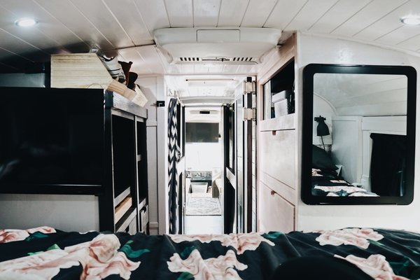 Looking back toward the front of the bus, more storage becomes visible. The pink dresser on the right holds the family's clothes. The gray dresser to the left incorporates a standing desk for Brandon and hides mechanicals.