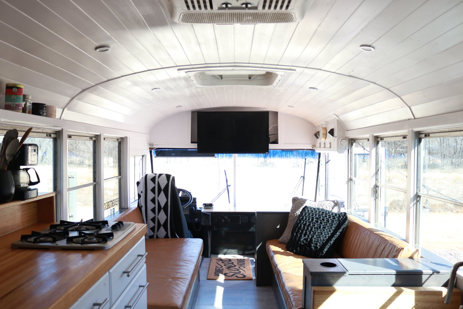 """Living Room, Sofa, Ceiling Lighting, and Vinyl Floor A look at the view toward the driver's seat and front of the bus. The family built two camel leather couches facing one another for the living area. A table can be placed between them for family meals. Built-in storage in the couch bases hold everything from extension cords and leveling blocks to board games and kettle balls. The armrests also open up and have outlets inside. """"I intentionally built the five-inch ledge behind the couches for our coffee in the morning,"""" says Ashley. """"The kids also use this ledge to play with their LEGO mini figs or their tech decks. It serves its purpose well!""""    Photo 8 of 15 in A 320-Square-Foot School Bus Becomes an Airy Abode For a Family of Five"""