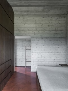 Custom walnut cabinetry in the sleeping area warms up the concrete shell.