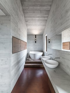 The use of walnut, red concrete, and reinforced concrete remains consistent throughout the master bath.