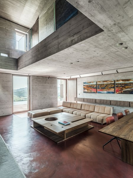 "While the exterior ""faithfully interprets the typical formal themes of this Italian region,"" says the architects, the inside is much more modern and minimalist. Reinforced concrete walls and ceilings meet a red concrete floor, which blends with the courtyard outside."