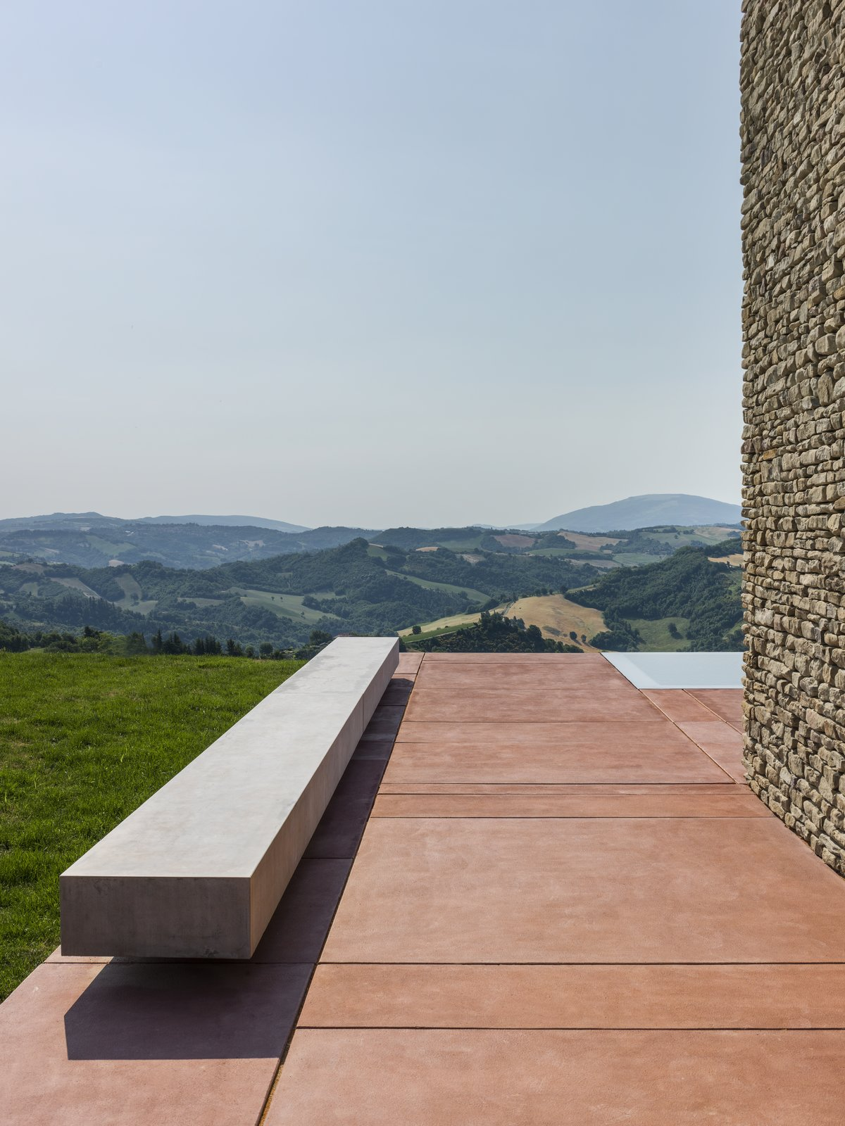Outdoor, Side Yard, Grass, Concrete, and Walkways The rectilinear form of a floating concrete bench sits atop the red concrete pad that defines the exterior courtyard.  Best Outdoor Side Yard Grass Photos from A Minimalist Residence Rises From Medieval Italian Ruins