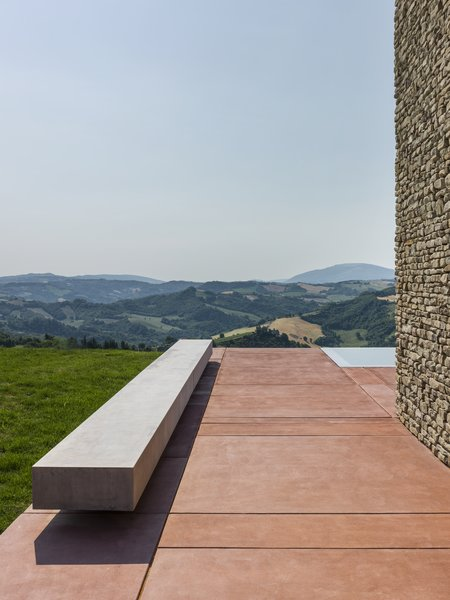 The rectilinear form of a floating concrete bench sits atop the red concrete pad that defines the exterior courtyard.