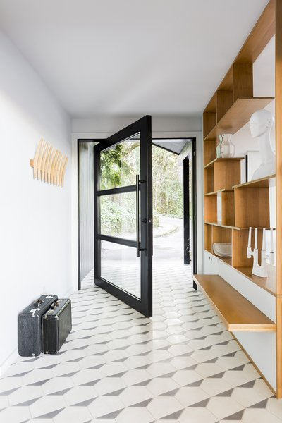 The entry floor now boasts the striking Hex Clip pattern from Clé Tile. Horner also installed custom shelving and a floating bench, both fabricated from birch plywood.