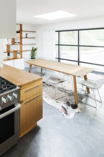 The wall of windows is original, while the floor received new concrete. Horner also specified a new stove and hood, as well as a new backsplash in large, textured field tile from The Surface Store in Portland.
