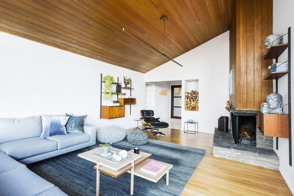 In the living room, the designers preserved the existing Douglas fir paneling on the ceiling and walls, the fireplace, and the firewood niche. The cooler tones in the sofa from Design Within Reach, rug from Kush Rugs, and knitted poufs from SMG Collective balance out the wood and dial up the cozy factor.