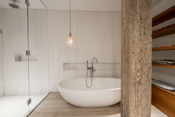 The walls in the shower and behind the tub are clad in slabs of Bianco Dolomiti marble. The floors are the same reclaimed bleached white oak used throughout the house. The light over the tub is the owner's, sourced from souks in Marrakech.